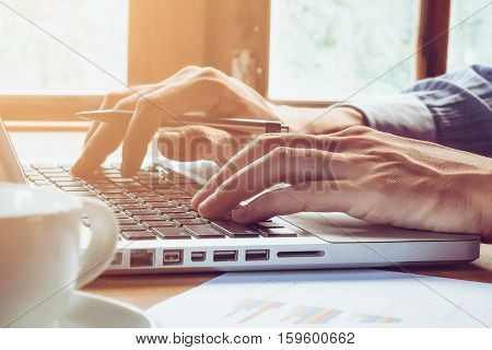 Business man hand holding pen and working with laptop on wooden table close up.Business concept.
