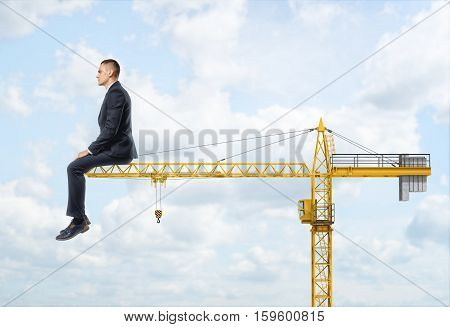 A huge businessman sitting on the end of a crane on the sky background. Dreaming about career growth. Building industry. Supervising manpower.