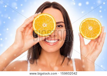 Happy Girl  Holding Halves Of Orange Near Face On Winter Background