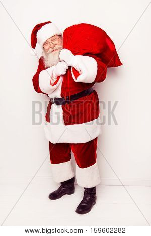 Funny Santa Claus Wearing Red Costume With Big Heavy Sack While Standing White Background