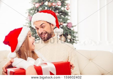 Excited little girl receiving xmas present fron her dad