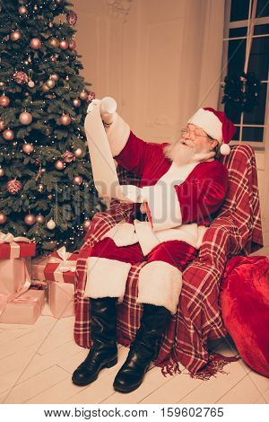 Santa Claus Wearing Red Costume And Black Shoes Holding List Of Children's Wish And Presents And Rea