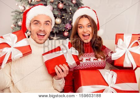 Happy Excited And Amased Couple Celebrating New Year And Holding Red Presents