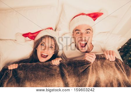 Top View Of Cute Amased Surprised Couple In Santa Hats Screaming In Bed