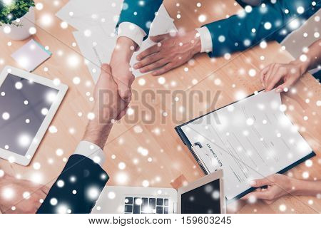 Handshake Of Two Business People On Snowy Winter Background