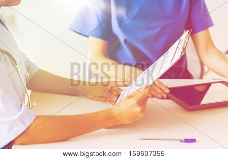 hospital, profession, people and medicine concept - close up of doctors with tablet pc computer and clipboard reading medical report at medical office