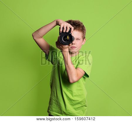 Photographer. Teenage boy using professional camera isolated on green background.