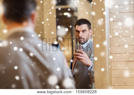sale, shopping, fashion, style and people concept - young man in suit with smartphone taking mirror selfie at clothing store over snow