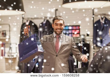 sale, fashion, retail, business style and people concept - happy man with shopping bags at clothing store over snow