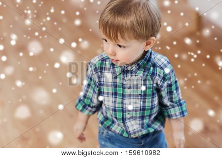 childhood and people concept - happy little baby boy at home over snow