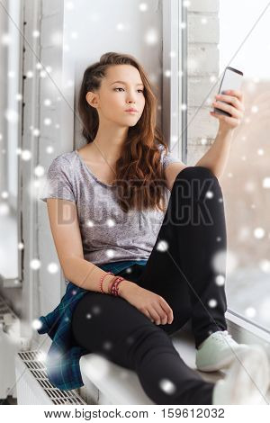 people, technology, winter, christmas and teens concept - sad unhappy pretty teenage girl sitting on windowsill with smartphone and texting over snow