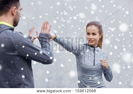 fitness, sport, martial arts, self-defense and people concept - happy woman with personal trainer working out strike outdoors over snow
