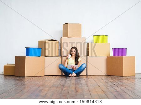 Young girl moving in a new home. Woman with boxes.