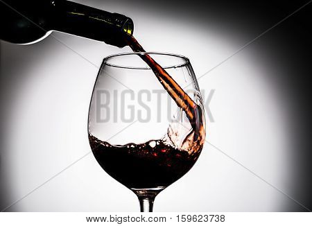 Red wine being poured from bottle in wine glass on empty background