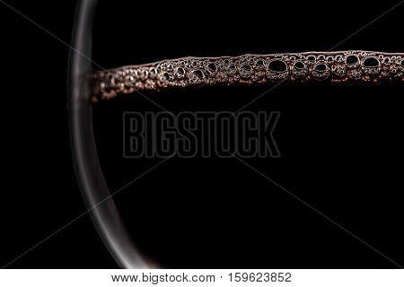 Red wine with bubbles on surface in glasses on black background empty