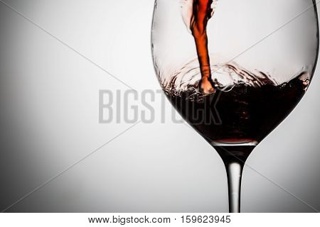 Filling wineglass of red wine closeup, image with space for text