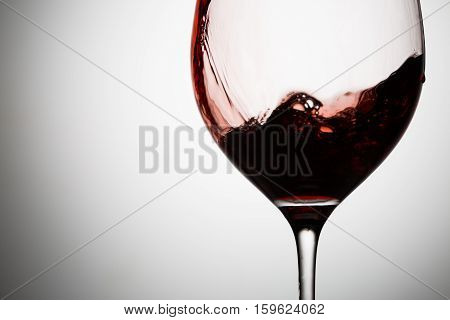Red wines wave flows down the wall of wineglass closeup. Taken in motion