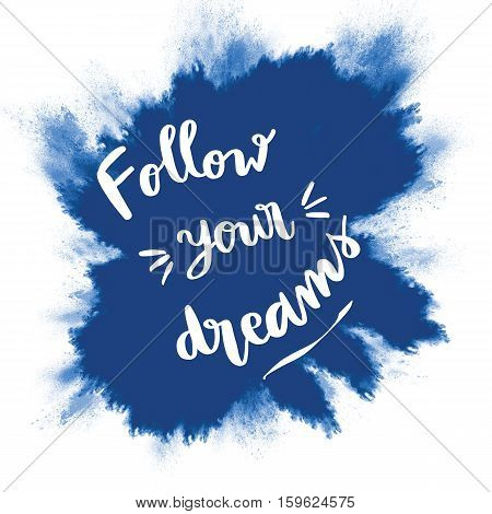 Follow your dreams inspirational message on blue splash background