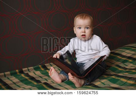 little funny boy reading book at home