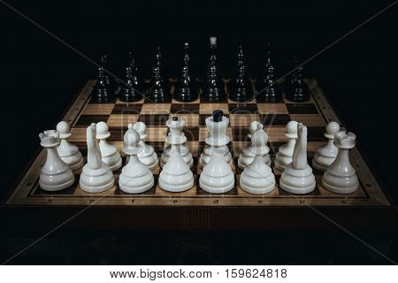 Chess board with figures on a dark background