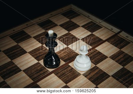 White pawn against the black king on the chessboard