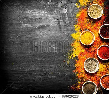 Big set of colored ground spices and herbs. On the black chalkboard.