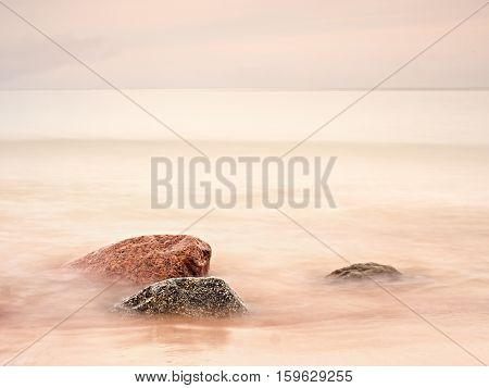 Long Exposure Of Sea And Big Boulders Sticking Up From Water Within Twilight Time.
