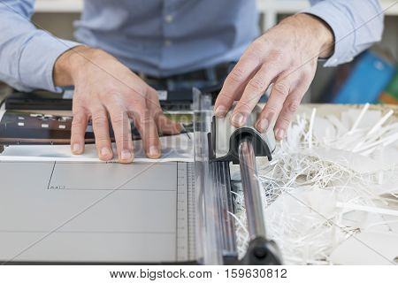 man cutting print with precision cutter on desk
