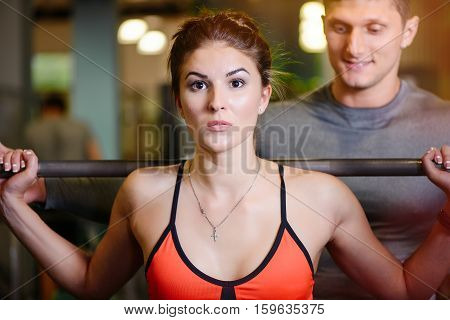 Fitness Girl With A Barbell Working With A Trainer