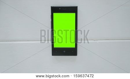 Smartphone with green screen on white wooden background