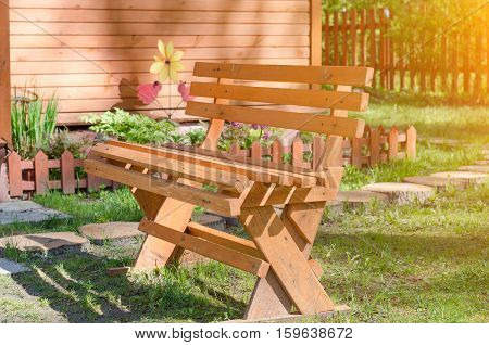 A bench in the alley in the park on a sunny day with a blurred background