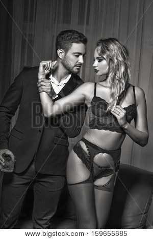 Sexy macho man holding blonde lovers arm sensuality black and white