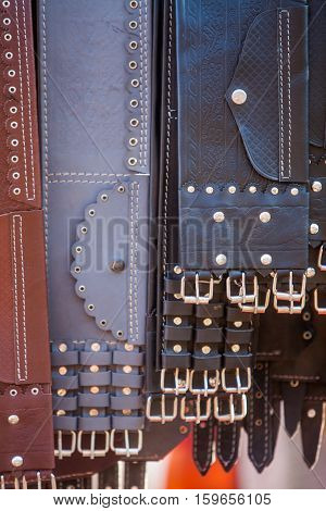 Color image of some leather belts on display.