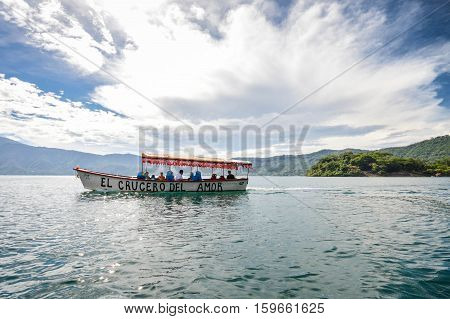 Lake Coatepeque El Salvador - May 23 2015: Tourist boat cruises the waters of the beautiful volcanic caldera Lake Coatepeque in El Salvador. Central America