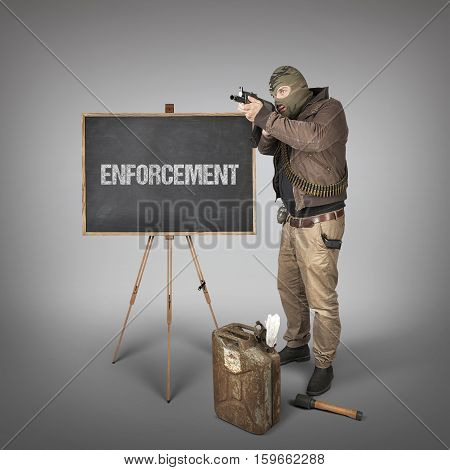 Enforcement text on blackboard with terrorist holding machine gun