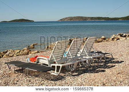 Beautiful Croatian beach with sun beds. Beach with clear crystal water.