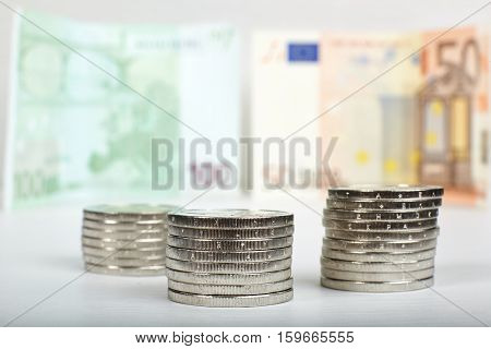 Euro coins stacks and banknotes as background.