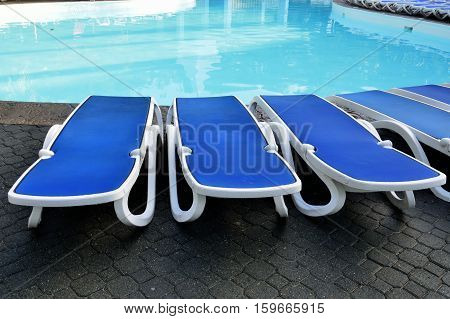 empty Sun beds by a swimming pool