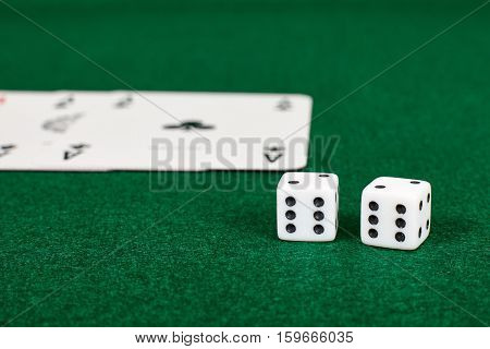 White dices and playing cards on green table.Illegal gambling.