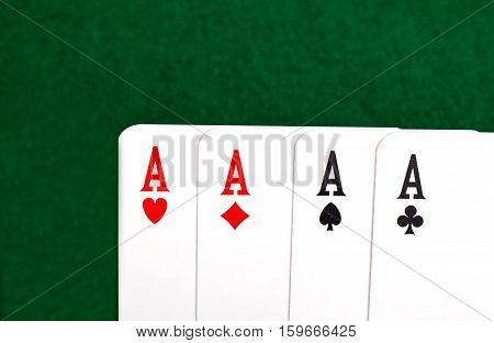 Four aces closeup view on green table.
