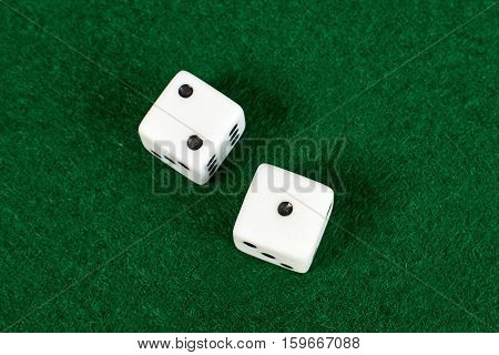 White dices close up view on green table.