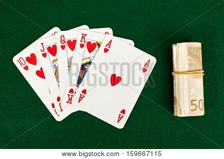 Poker cards and roll of money on green table.