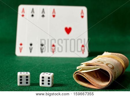 White dicesa roll of money and four aces on green table.Illegal gambling.
