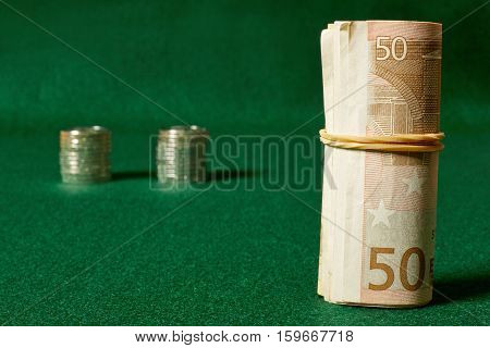 Roll of money and coins stacks on green table.