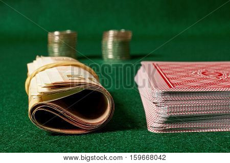 Poker cards coins stacks and roll of money on green table.