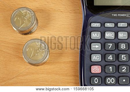 Stacks coins and calculator on wooden background.