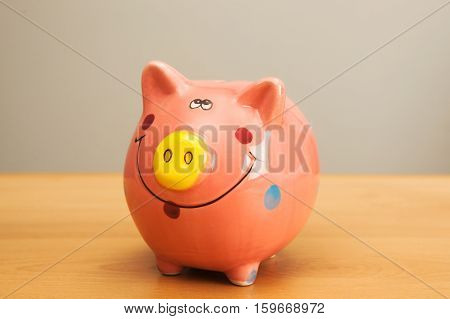 Pink piggy bank on wooden table background.
