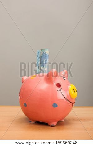 Banknote in a pink piggy bank on wooden table.