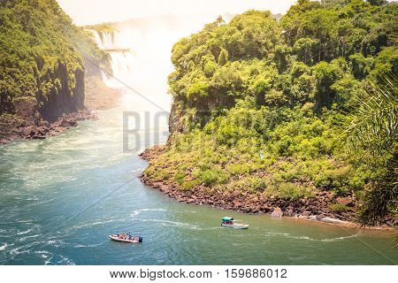 Detail of Iguazu Fall from mirador of Isla San Martin between argentinian and brazilian river side with motorboat dinghy - Waterfalls nature wonder of South America continent - Vivid saturated filter