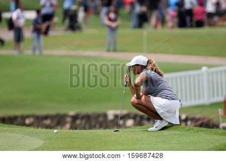 KUALA LUMPUR, MALAYSIA - OCTOBER 29, 2016: Cheyenne Woods of the USA checks the line of her putt at the TPC Golf Course at the 2016 Sime Darby LPGA Malaysia golf tournament.